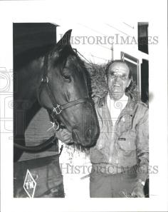 Trainer extraordinaire Woody Stephens poses with one of his champions, Creme Fraiche.