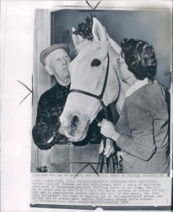 "Greyhound stands under mistletoe held by Vernor (""Dooley"") Putnam and his wife, Leona. The greatest trotter of all time turns 33 on New Year's day."