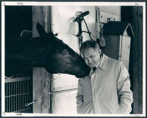 The legendary trainer, King T. Leatherbuy, gets a smooch from one of his horses.