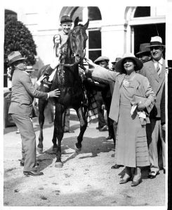 TWENTY GRAND is led in by his owner, Mrs. Payne Whitney, after winning the 1931 Belmont Stakes. The colt also won the Kentucky Derby that year.