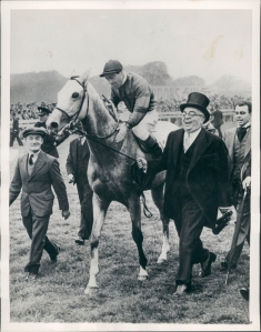 His HH the Aga Khan III shows his delight as he leads his Derby winner in. TAJ AKBAR had come in second.