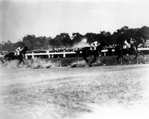 "Man o'War (1) passes the Saratoga stands for the first time leading his only competitors from the powerful Harry Payne Whitney stable, John P. Grier (3) and Upset (2). Man o' War won ""under restraint through the stretch"" as Upset passed his tiring stablemate to gain second place at the finish."