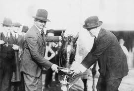 Mr. Samuel Riddle and trainer, Louis Feustel, hold the gold cup while Man O' War takes a long drink.